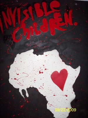 a black painting with a white cutout of africa that has a red heart