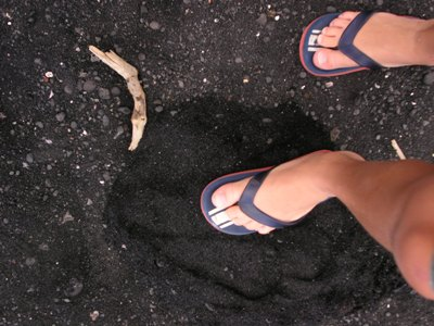 a photo of flip-flopped feet on black sand beach