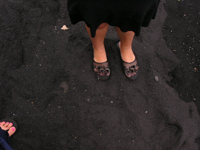 a photo of sandaled feet on black sand beach
