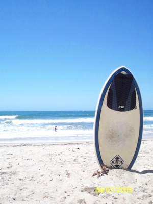 a skimboard stuck upright in the sand