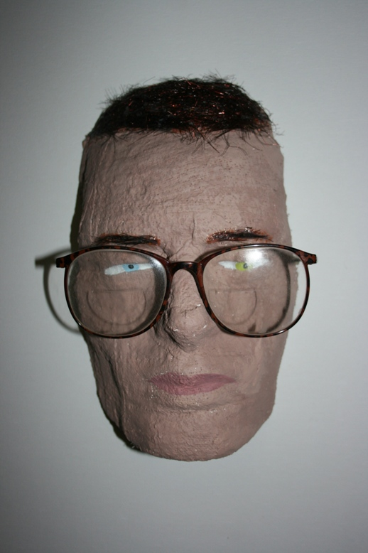 a papier mached face with glasses