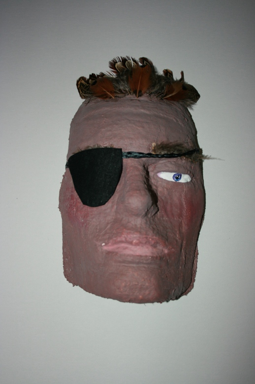 a papier mached face with eyepatch and feathers